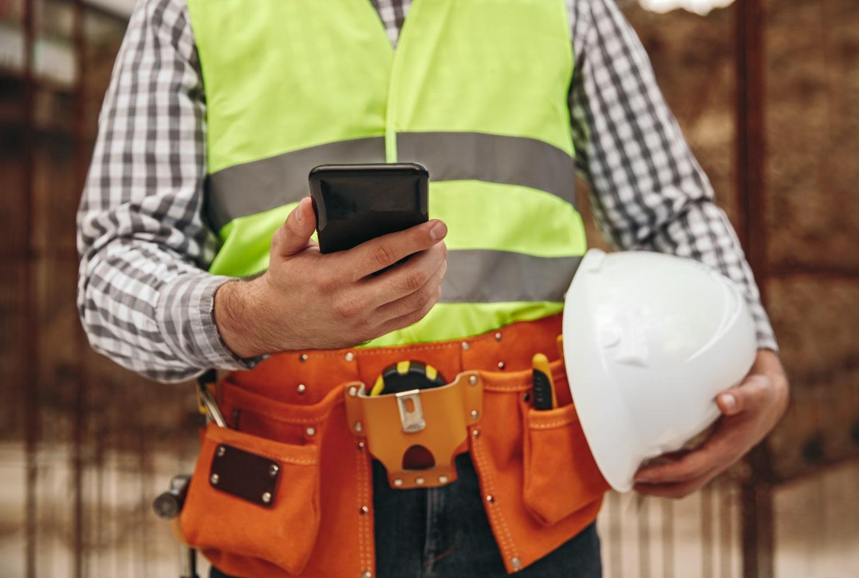 Bauarbeiter auf Baustelle nutzt App für moderne Workflows auf dem Bau