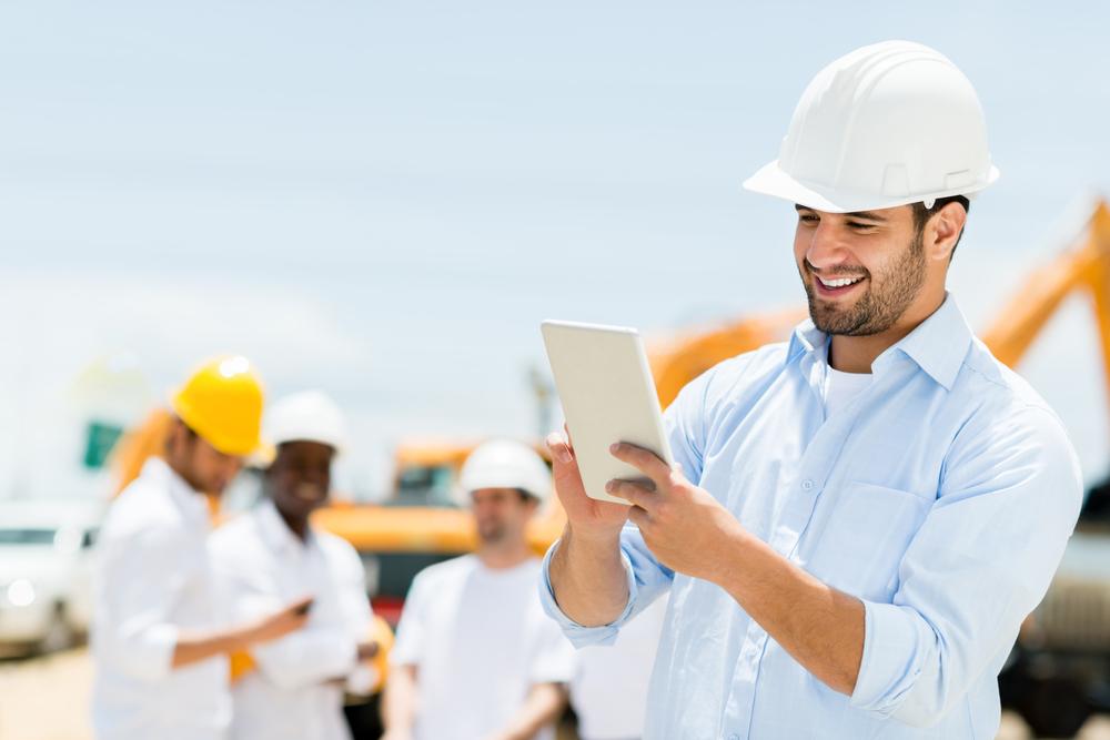 Mann auf der Baustelle mit einem Tablet in der Hand